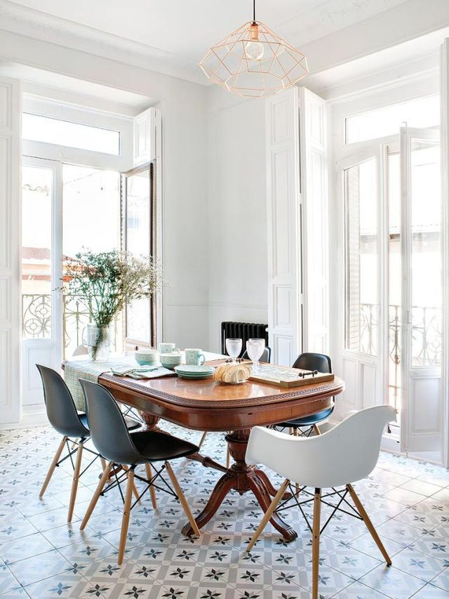 Art deco style kitchen featuring mosaic tiled floors, a wooden dining table, mixed molded chairs and white walls with natural light | Ateliers HR
