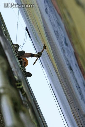 Un pintor da los últimos brochazos al mural de 48 metros de alto sobre el edificio Colpatria, del centro de Cali. Foto Julio Sánchez.