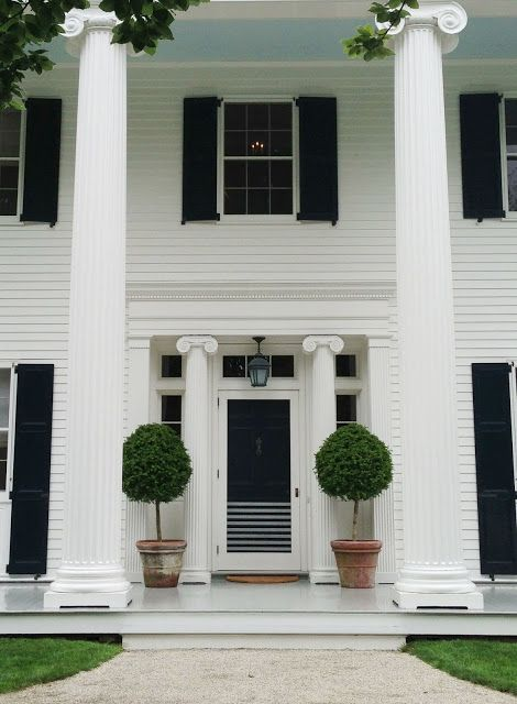 Exterior of Aerin Lauder's South Hampton home complete with Ionic columns and large topiaries