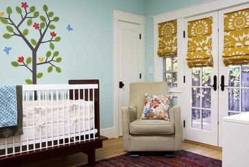 This nursery is using roman shades on a french door to keep the lighting out or in. The color of the drape fixes well with the rest of the room .