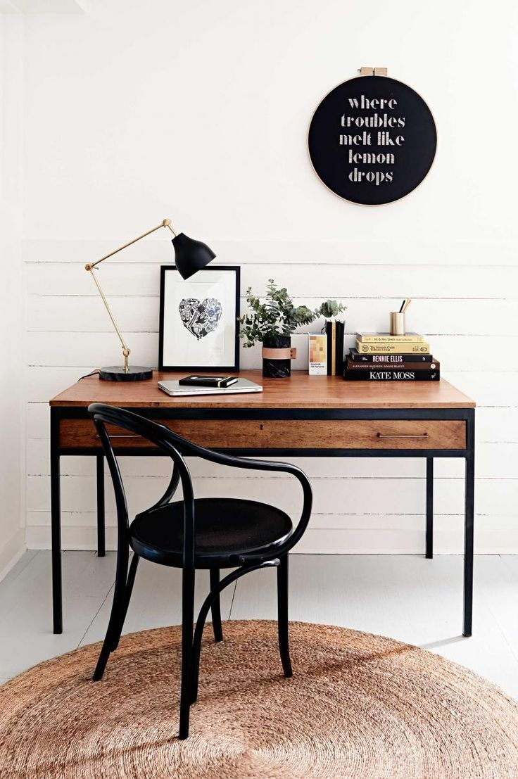 Workspace: white wood horizontal wall panelling, wooden desk with long drawer and black metal frame, black Thonet armchair, black desk lamp, white painted floorboards, black typographical art