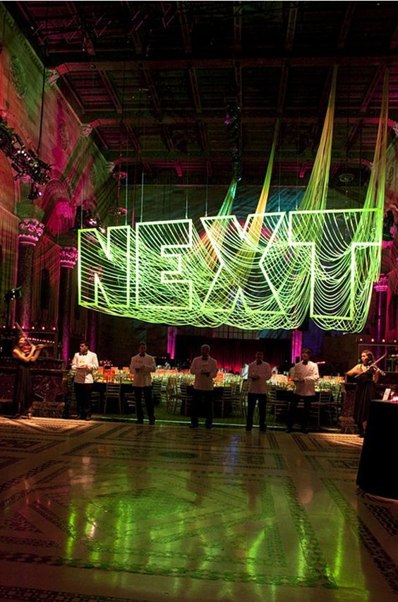 Welded steel, florescent flagging tape dramatically draped from all points along the type - by David Stark | Event Lighting