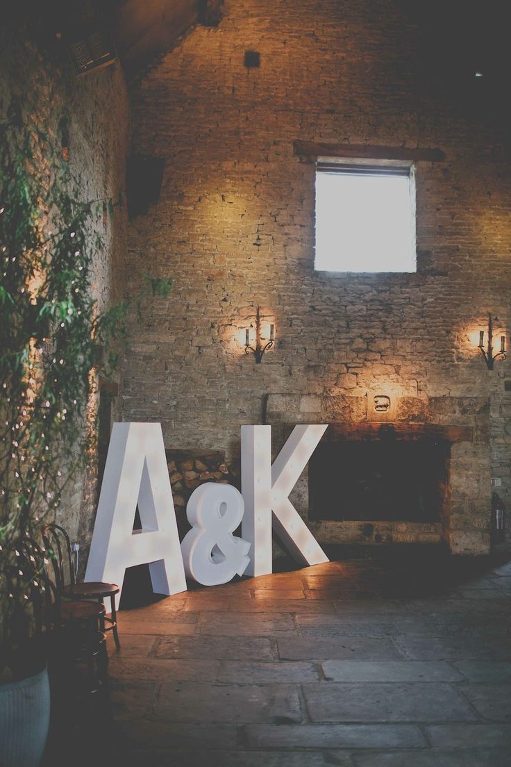 Rustic Cripps Barn wedding venue with giant light up letters - Image by Josh Tollafield Photography - A Maggie Sottero Wedding Gown with gypsophila baby's breath flower crown for a wedding at Cripps Barn including Coast forest green bridesmaid gowns.