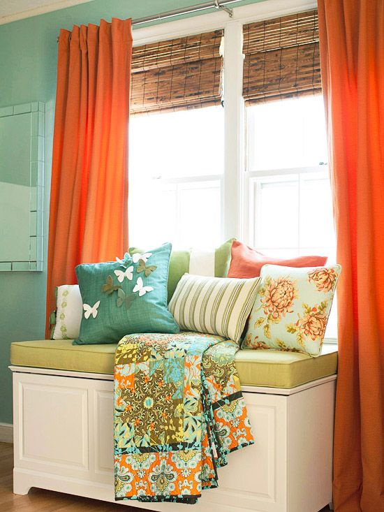 Bamboo blinds layered with orange panels control of amount of light streaming in. The chest serves as storage for blankets and linens and also acts as a window bench. #orange #turquoise