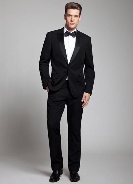 El hombre lleva un vestido negro y camisa blanca y corbatin negro y zapatos negros