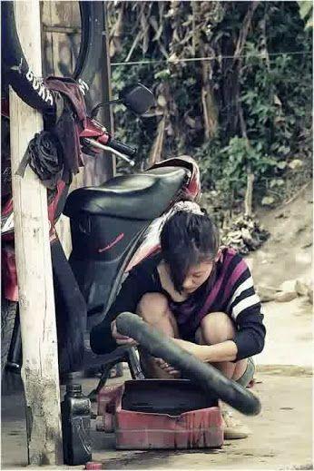 Seorang gadis remaja berparas ayu dengan terampil mampu menambal ban sepeda motor.