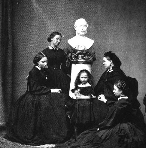 Mourning photo: Queen Victoria's five daughters (Beatrice, Alice, Helena, Victoria & Louise). The bust is of their father, Prince Albert, who died in 1861. Photograph dated 1862.
