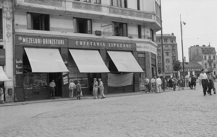 """Strada Lipscani, colț cu Bulevardul 1848 (azi Brătianu), 1956.  Lipscani este una dintre cele mai vechi zone negustoreşti din Centrul Istoric, dar a fost cunoscută de mult sub denumirea de """"Uliţa Mare"""", artera care făcea legătura între marile drumuri comerciale ale României. Prima menţiune documentară a """"Uliţei Mari"""" este făcută în anul 1589. La scurt timp după acest moment, strada a fost populată de tot felul de negustori, care şi-au înfiinţat magazine, prăvălii şi hanuri."""