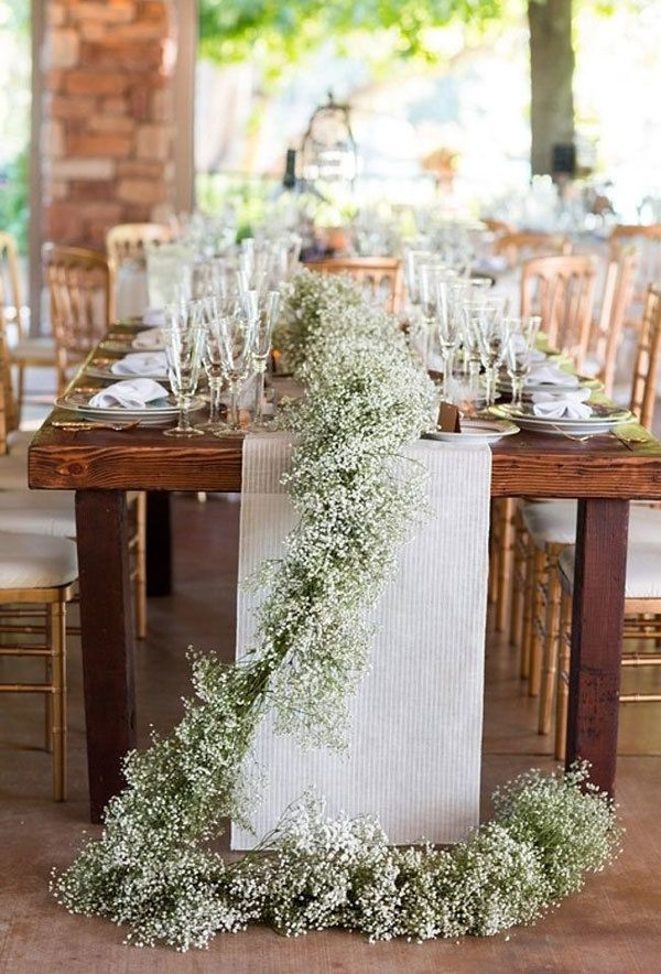 Long baby's breath table runner draped across long wooden table and onto floor.