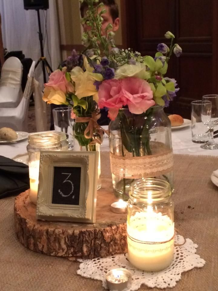 Table centre pieces Flowers by Angels Florist Numbers, wood, hessian, doilies and candles by Rhapsody Wedding Planning + Coordination http://www.rhapsodyweddings.blog.com