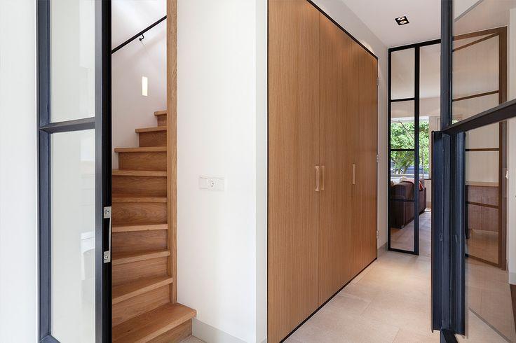 Bloem en Lemstra Architecten maakte het ontwerp voor een maatwerk inbouwkast. De kast bevat een ruimte garderobe en zelfs een ruime berging onder de trap. De combinatie van de eiken houten kastdeuren, de zwart stalen deuren, een zandkleurige tegelvloer en een strakke eiken trap zorgt voor een modern en warm geheel. Ontwerp BNLA architecten | Fotografie Wim Hanenberg