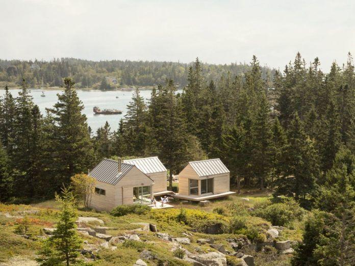 Fotografia kolorowa. Na zdjęciu wśród iglastych drzew znajdują się trzy malutkie białe domki o szpiczastych dachach. Między drzewami, z domkami, widać rzekę, po której pływają drewniane łódki.