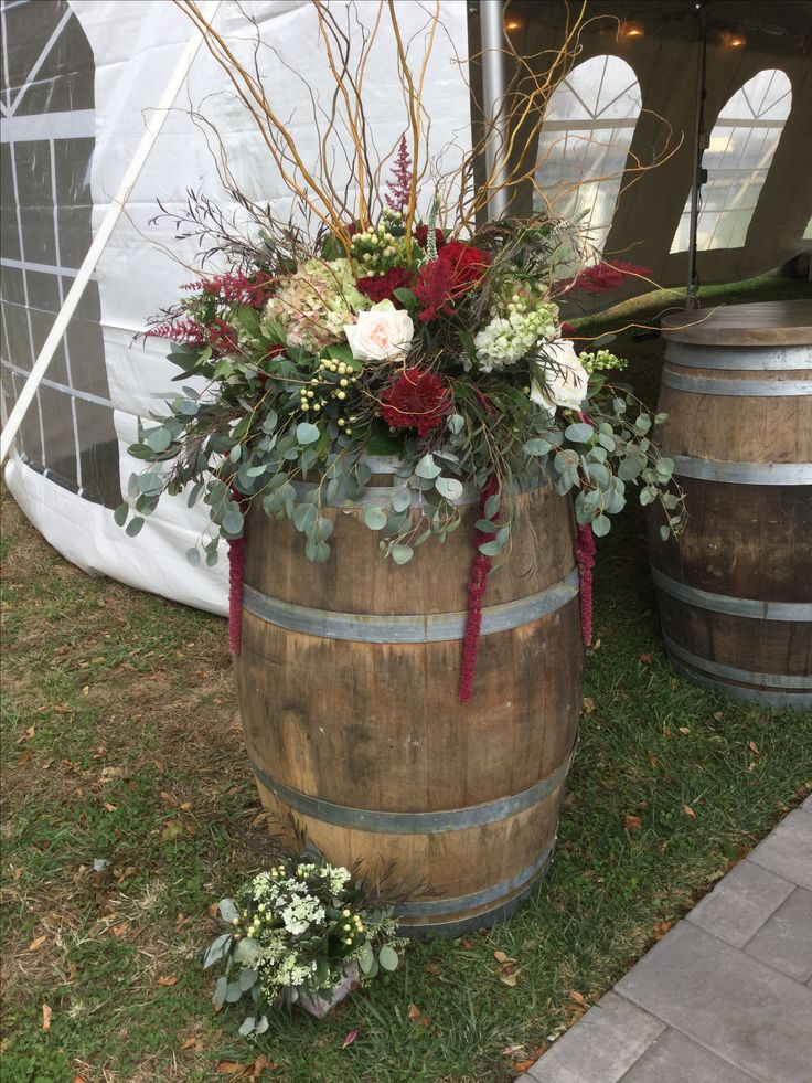 Vineyard themed wedding with rustic arrangements on oversized wine barrels. Lush black magic roses, antique hydrangea,  blush roses, burgundy astilbe, curly willow, hanging amaranths and draping silver dollar. Contact Marion at Bayview Florist Wedding Studio in Sayville, NY. Maz851@aol.com