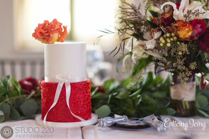 Two tier modern, elegant sparkly red glitter wedding cake with red/orange/yellow fire rose (sugar). Small cake for the wedding party table. The base tier looks like Dorothy's ruby slipper! Cake design: enticing-icing.com | Photography: studio220photography.com