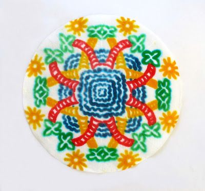 After folding rice paper into pie-shaped wedges, the children paint designs on one side, then turn the wedges over and paint the mirror image. When the paper is unfolded, intricate patterns are revealed. Age 12
