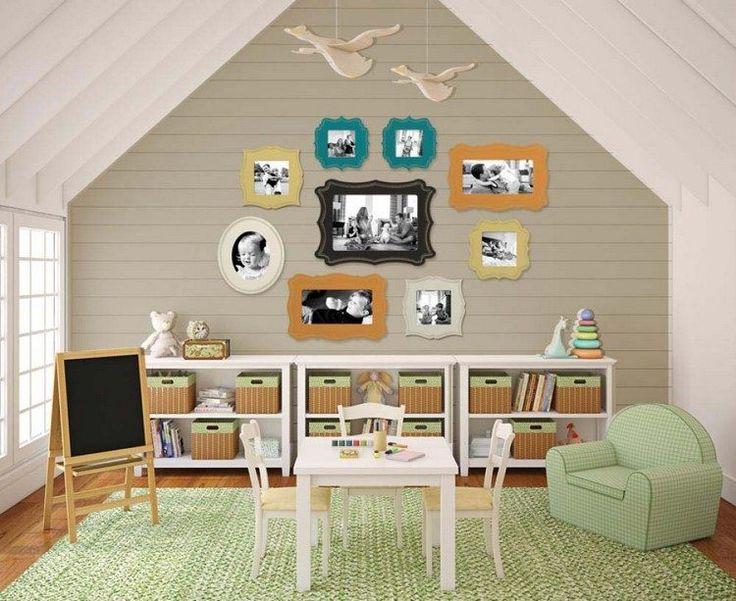 salle de jeux enfant accueillante aménagée avec un tapis et un fauteuil vert clair, un meuble de rangement à boîtes en osier et un mur décoré de photos en cadres originaux