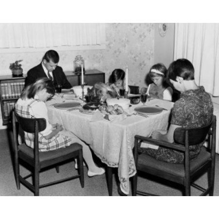 Mature couple with their three children praying at a dining table on Thanksgiving Day Canvas Art - (18 x 24)