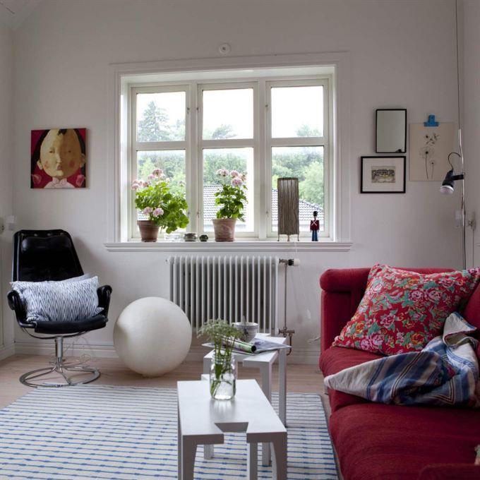Soffmys.Tv-rummet används inte så  mycket på  sommaren men på  vintern  älskar familjen att hänga här. Röd soffa från Eilersen, Jetsonfåtölj från Dux. Tavla med flicka av konstnären Xu Jie från Shanghai.