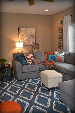white curtains, peach walls, red pillow with blue couch
