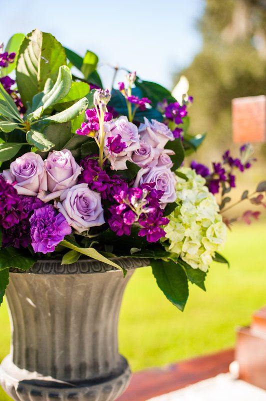 detail of large arrangement for outdoor altar table. urn is filled with lavender roses, purple stock, lavender and purple carnations, hydrangea,  variegated pitisporum and lemon leaf.