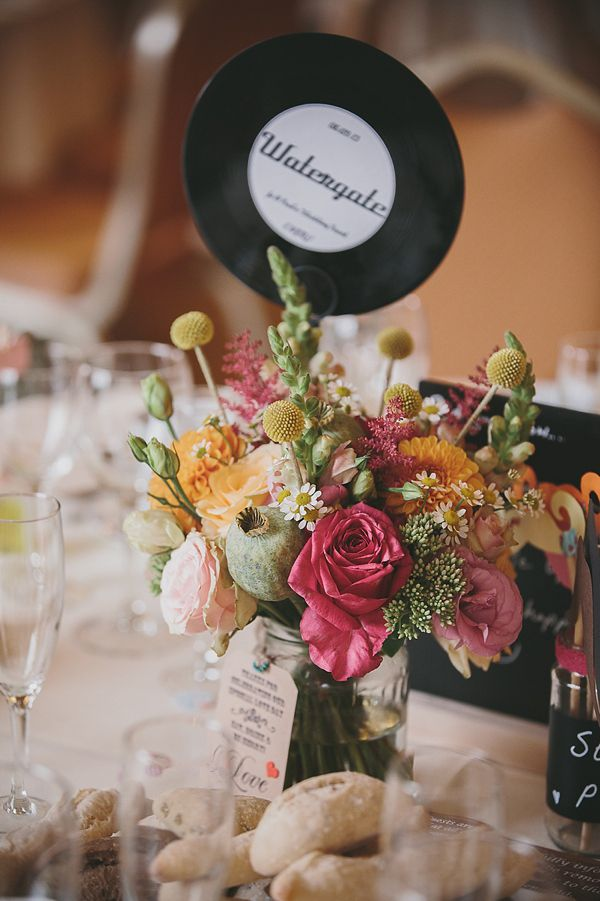 Gorgeous floral table centre piece using vinyl records as table names. From 'An Original 1950s Vintage Gold Wedding Dress For A Fun And Colourful Italian Inspired Wedding'. http://www.mckinley-rodgers.com/