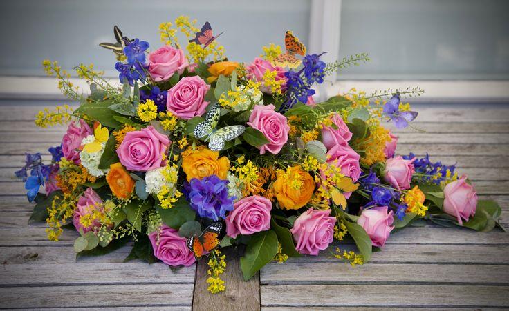 Rouwstuk in druppelvorm met gemengde kleuren en vlinders / Casket spray with colorful flowers and butterflies