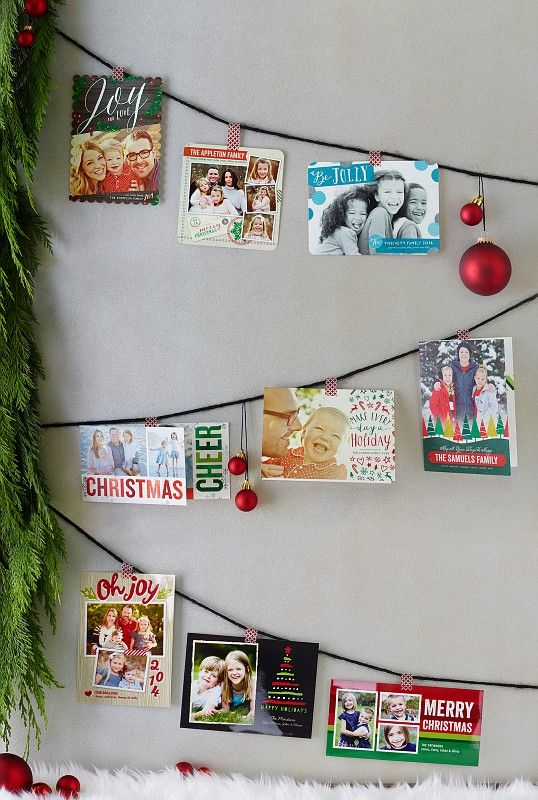 String your holiday cards along a wall in a festive layout display. We love the ornaments that sit between our favorite designs. | Shutterfly