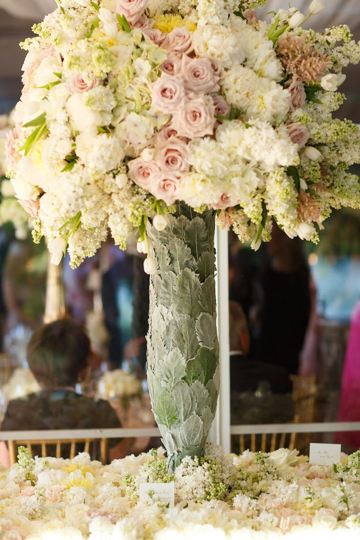 A tall, unique centerpiece brimmed with pastel florals. Photography: Karlisch Studio. Read More: http://www.insideweddings.com/weddings/southern-chic-wedding-in-oklahoma-with-performance-by-boyz-ii-men/697/