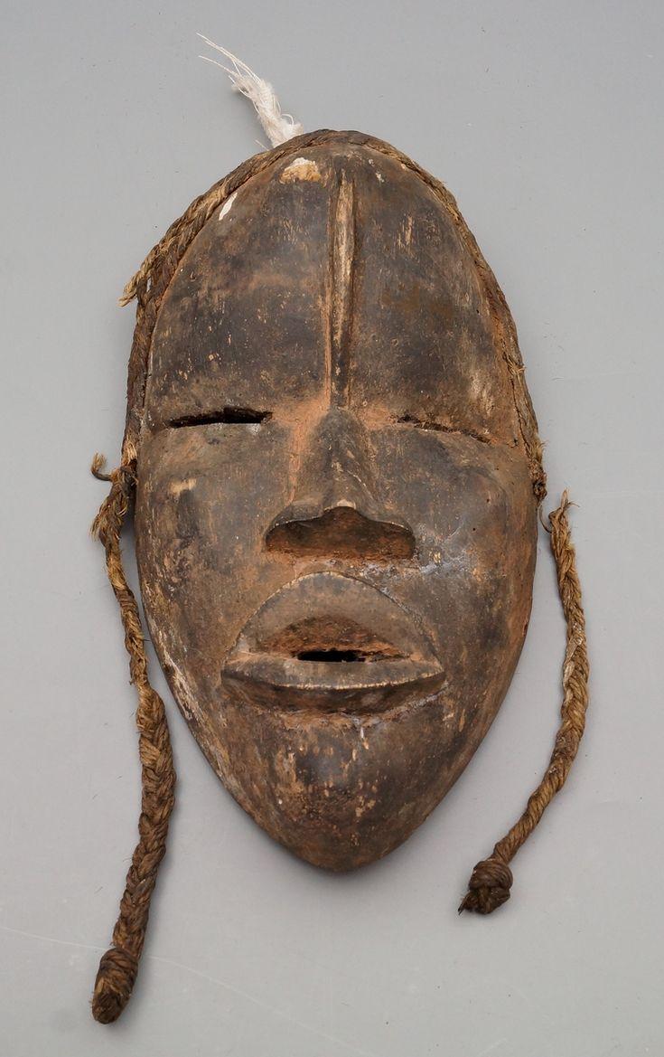 Een houten Dan stijl masker van een mannengezicht met gevlochten raffia haar, Burkina Faso, ca. 1900/1920