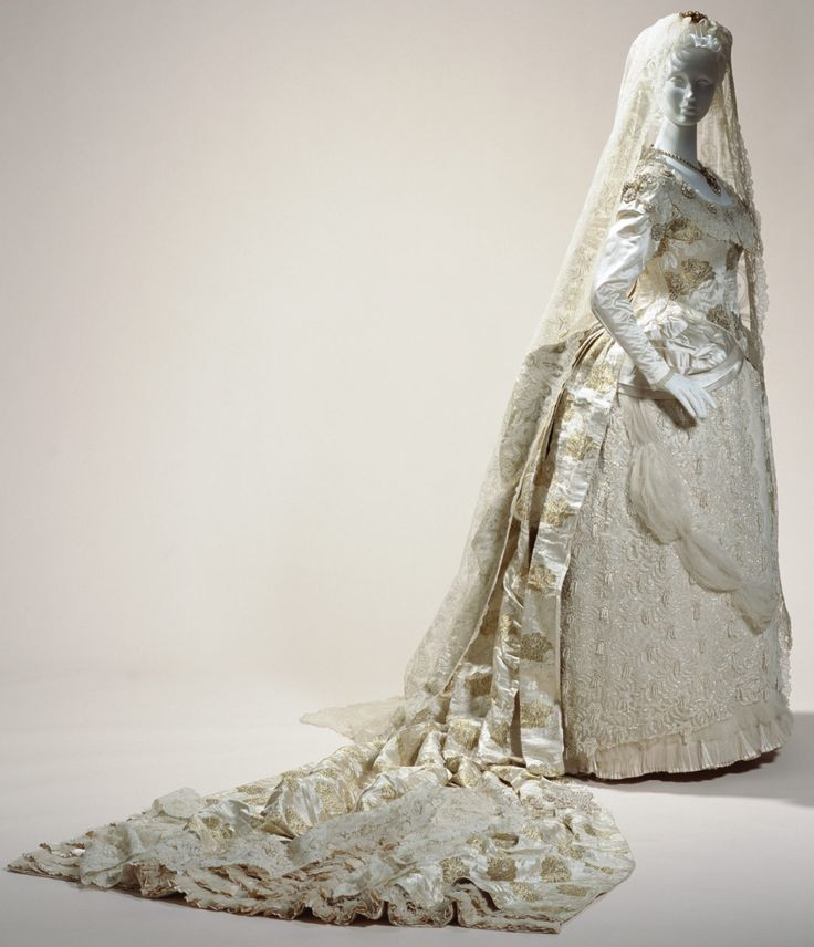 Wedding Dress  1882 This wedding dress of luxurious silk brocade demonstrates the latest trend of its time, the bustle style. The abundantly gathered draping, as well as the ornaments concentrated with lace, flounce, and embroidery techniques that decorate the 2.4 meter-long train indicate that the wearer was a woman of the upper classes. Traditionally, wedding gowns in the West were not limited to using the color, and brides simply wore gorgeous, fashionable outfits. However, from the 19th…