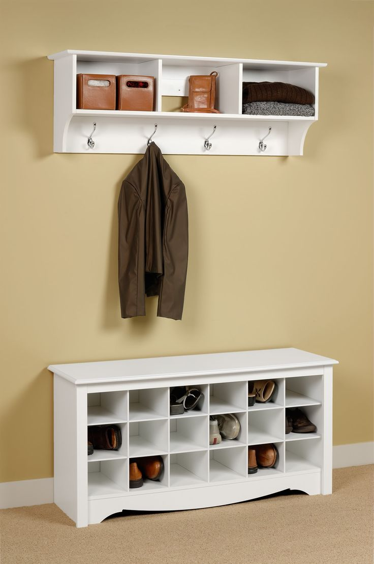 Rectangle white wooden wooden shoe rack on the floor connected by white wooden coat rack on cream wall
