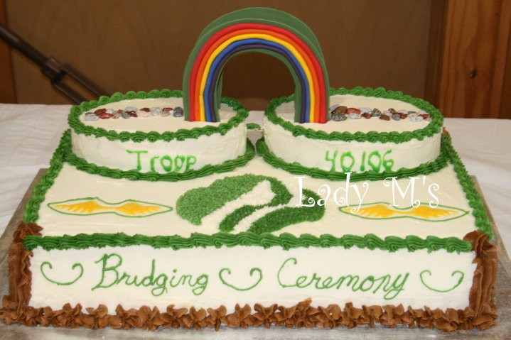 """Brownie bridging to Jr. Girl Scout - It's the end  of the year and the troops are moving up and on.  This is/was our Brownie troop """"bridging"""" ceremony.  The rainbow is double sided with a bridge in the middle made purely of fondant, no extra support structure, and candy rocks for the path. I tried to use the Wilton sparkles gel, it ran.  The rest is all butter cream frosting.   Thanks for looking and happy creating! (My 9 year old helped with the bottom of the cake, brown.)"""
