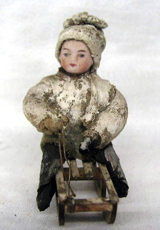 Antique snow baby child on sled Christmas ornament. Cotton with bisque face.