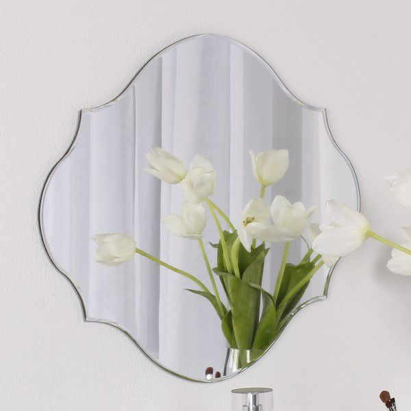 Create the illusion of space and decorate in contemporary style with this classic frameless mirror. Perfect for small spaces, this mirror displays flat against the wall to bring in reflective light and space. This accent mirror works well in any room of the home with its unique scallop shape, classic beveled glass, and contemporary frameless style. Hang it above a fireplace, over an accent table, in a hallway, or use it as a vanity in a bathroom. This mirror is easy to install with hanging…