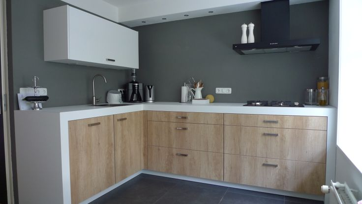 Waarin een kleine keuken groot kan zijn. Op maat gemaakt, met als doel: een keuken  creëren waarin het gezellig vertoeven is en geen passtukken worden gebruikt.  Het witte blad loopt  zijdelings door tot op de grond wat voor een ruimtelijk effect zorgt, hierbij de warme robuuste keukenfronten insluitend. Rust, ruimte en een warme huiselijke sfeer zijn de opbrengsten. Het Keukenbureau Harderwijk