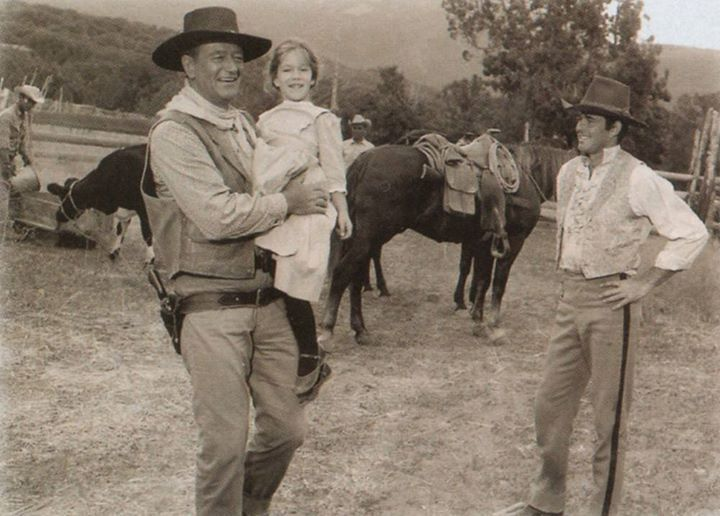 2a8d54a2 Duke holds daughter Aissa while Stuart Whitman looks on during a break in  the filming of