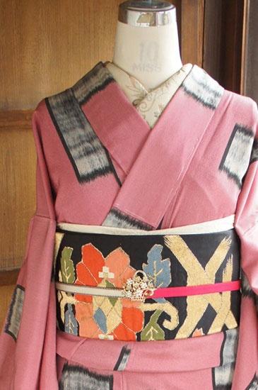 ほのかにスモークがかったようなこくのあるピンク色の地に、黒で縁取りされたグレーの四角モチーフがリズミカルに織り出された正絹御召の袷着物です。