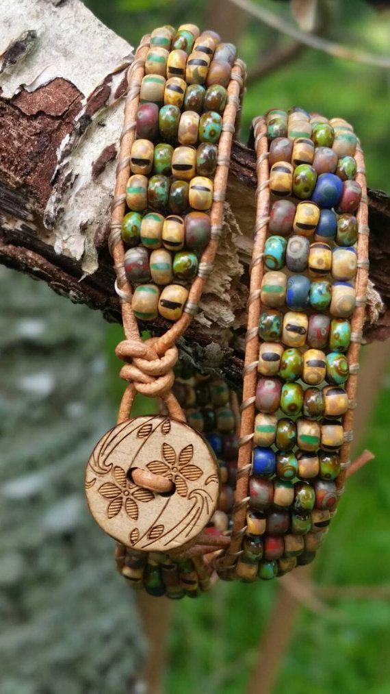 Smoothly soft and natural leather cord is the backdrop for the matte yet earthy vibrant Czech glass beads. This leather bracelet wraps twice, and closes with a wooden flower power button. At about one inch wide, this bracelet feels good to wear.
