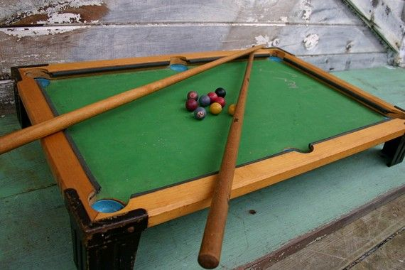 Vintage Toy Pool TableToy wooden pool table from the 40's or 50's. Constructed with a wooden frame, metal legs, metal cups for the pockets, rubber strips as the bumpers and green painted wooden playing surface. Includes two wooden pool cues and 9 wooden balls