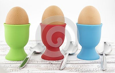Brown boiled chicken eggs in green, red and blue silicone egg cups with metal spoons for breakfast.