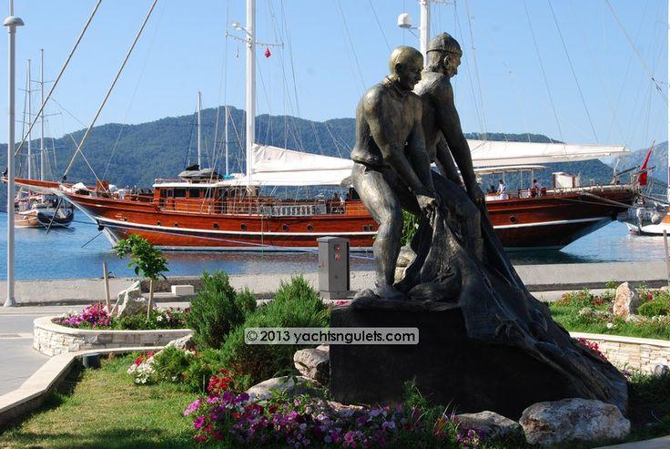 Fisherman's Statue Marmaris. Backdrop is the elegant VIP gulet Mare Nostrum.