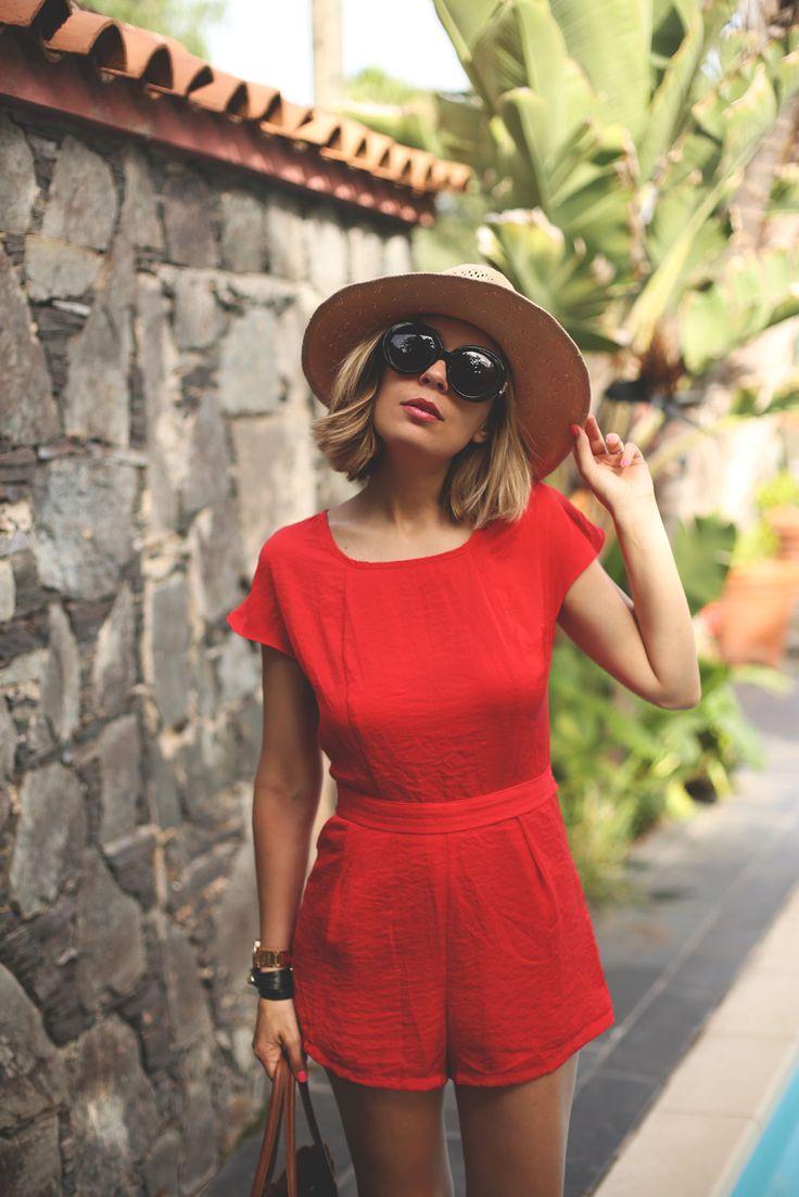Chica usando un romper en color rojo y complementándolo con lentes y sombrero