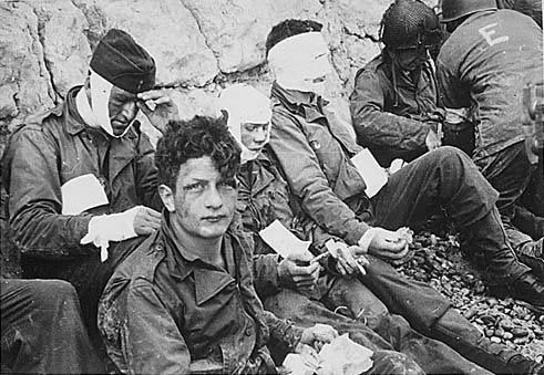 Soldiers of the 16th Infantry Regiment, wounded while storming Omaha Beach, wait by the chalk cliffs for evacuation to a field hospital for treatment. (Photo: US Army/Flickr