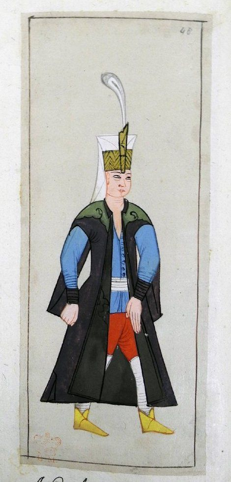 Seferli. A Janissary on campaign. Has a plume in the plume-holder on his Janissary head-dress. Dark purple kaftan with black lining and very long sleeves. Pale blue tunic, white kuşak, red knee breeches, white stockings and yellow ankle boots.