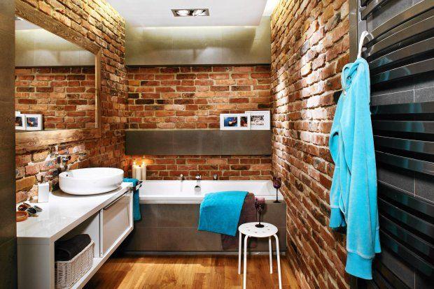 Wnętrze oświetlają sufitowe halogeny oraz taśmy LED zainstalowane za załomem podwieszonego sufitu, pod półką i w cokole wanny. Te dwa ostatnie punkty świetlne znakomicie kreują relaksujący klimat. Drewniana rama dużego lustra, dopasowana kolorem do ceglanej ściany, idealnie się w nią wtapia.