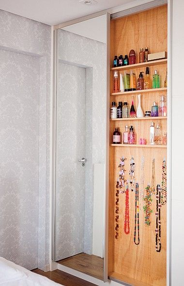 O espaço entre um pilar e o banheiro deu origem ao armário estreito com porta de correr. Os perfumes ficam em prateleiras de 10 cm de profundidade. Para pendurar os colares, a arquiteta Tatiana Yokota usou ganchos adesivos