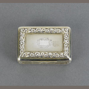9 - A George III silver gilt snuff box,  by Pemberton & Mitchell, London 1817,  rectangular form, engine turned decoration, the cover with a rectangular reserve, raised floral surround, the sides embossed with berry and leaf borders, length 7cm, weight 3oz.  Sold for £240 inc. premium  15 May 2007 11 a.m. London, Knightsbridge  Silver & Objects of Vertu including Post-War Silver  Auction 14895