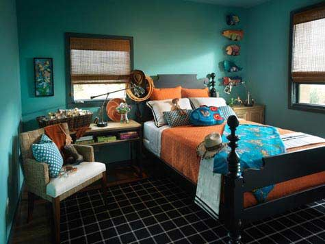 This boys bedroom has rich, saturated colors that are very warm and inviting. The choice of a warm blue wall color and bright accessories keep this room from feeling drab.