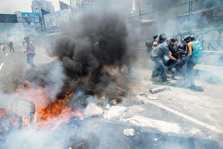 Venezolanen zijn over hun angst heen - NRC. Een groep fotojournalisten helpt verslaggever Román Camacho. Hij heeft een gebroken been omdat een militair hem aanviel met traangas.Foto Gabriel Osorio.