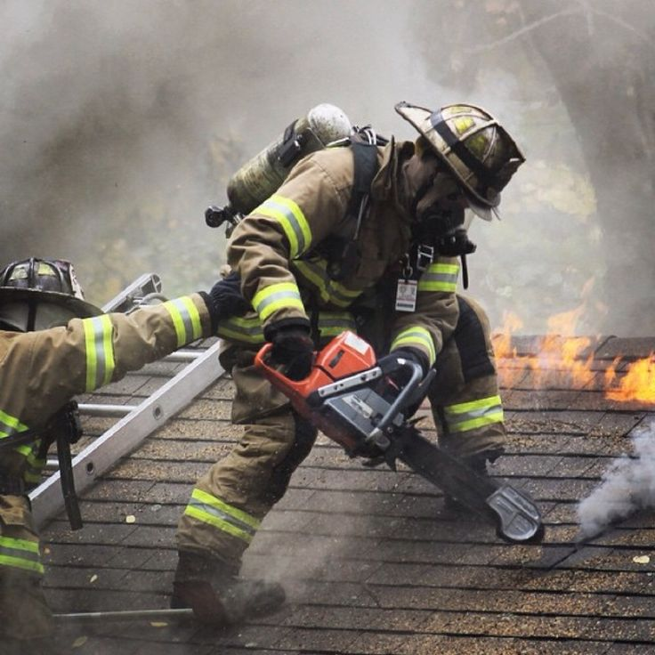 Firefighter Ventilating A Roof With A Chainsaw